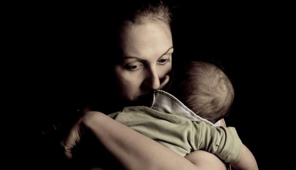 Donna stringe tra le braccia il proprio bambino