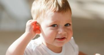 Bambino che presta attenzione mettendo una mano sull'orecchio