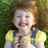 Bambina che mangia sdraiata di schiena su un prato