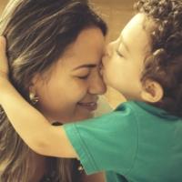 Bambino che con empatia bacia la madre sulla fronte