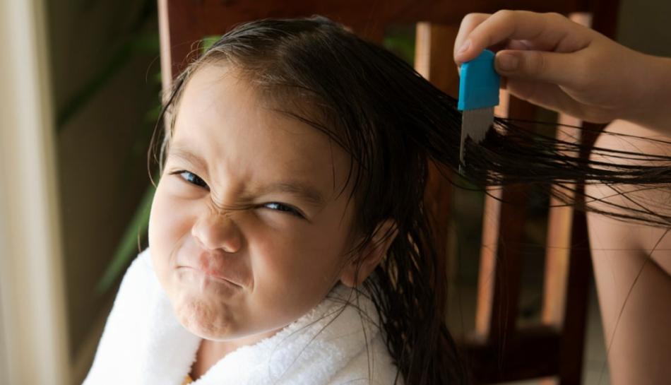 Bambina colpita da pidocchi con pettine a denti fitti