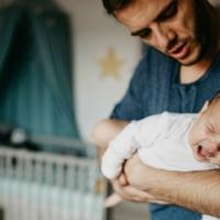 Padre culla il bambino dolcemente, evitando rischi di sindrome del bambino scosso
