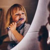 Bambino che si lava i denti allo specchio