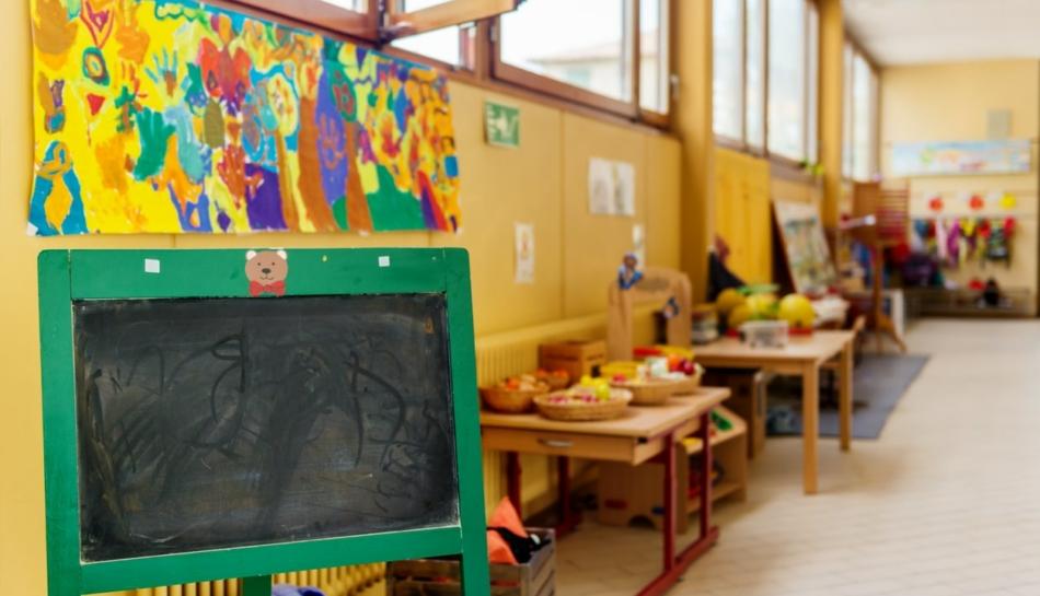 Aula di una scuola dell'infanzia o di un nido con lavagna in primo piano