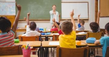 Bambini in una classe di scuola elementare che alzano la mano