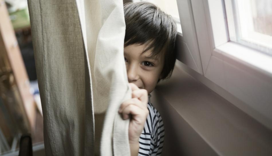 Bambino che per privacy si nasconde dietro a una tenda