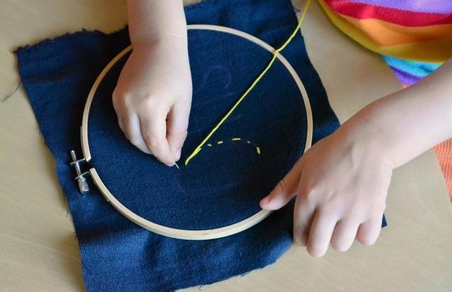 Bambino si esercita con ago, filo e feltro