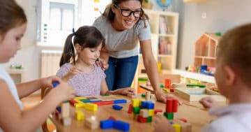 Maestra gioca con bambini alla scuola dell'infanzia