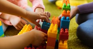 Mani di bambini che giocano con le costruzioni all'asilo nido