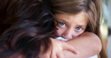 Primo piano di una bambina che abbraccia forte la mamma