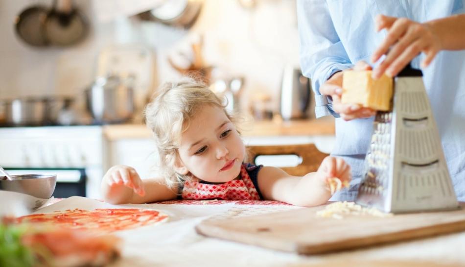 Bambina che aiuta la mamma a preparare il cibo