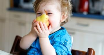 Bambino assaggia una pera