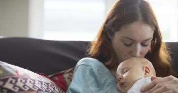 mamma che coccola il proprio neonato seduta su un divano