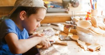 Bambino lavora con attrezzi sul tavolo