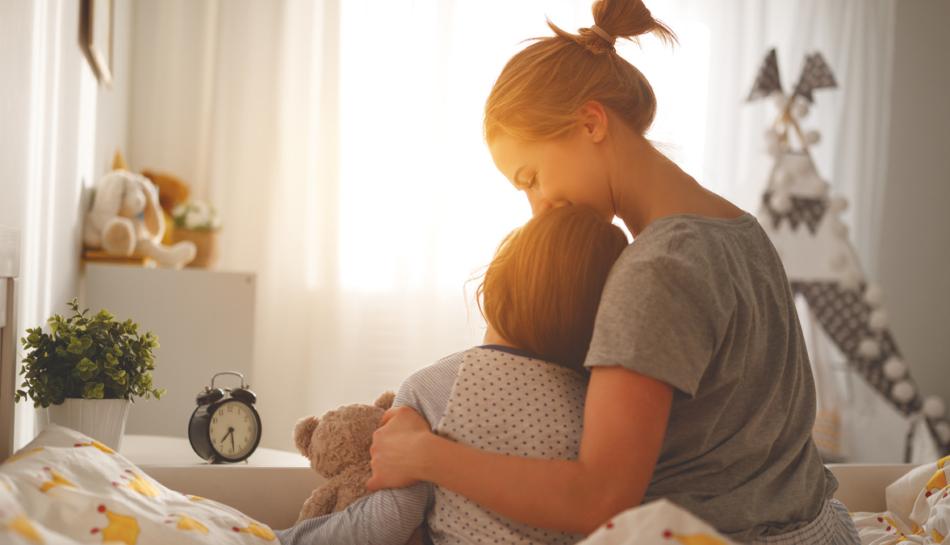 Mamma e bambina di schiena abbracciate sul letto