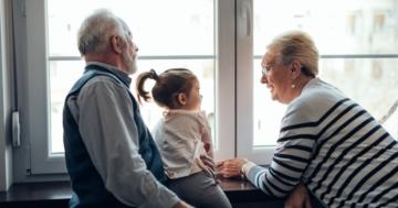 Nonni di spalle con la nipotina guardano dalla finestra