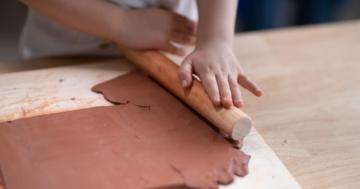 primo piano delle mani di una bambina che lavora l'argilla
