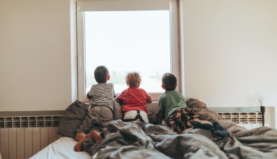 Bambini guardano attraverso la finestra durante la quarantena
