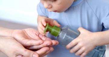 Primo piano di un bambino che versa del sapone sulle mani di un genitore