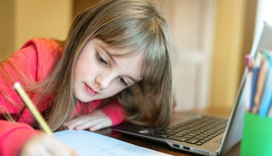 Bambina che scrive e segue al computer la didattica a distanza