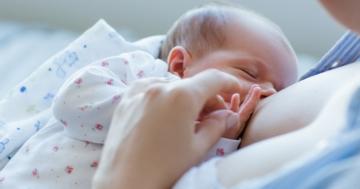 Neonato si nutre di colostro dal seno della madre