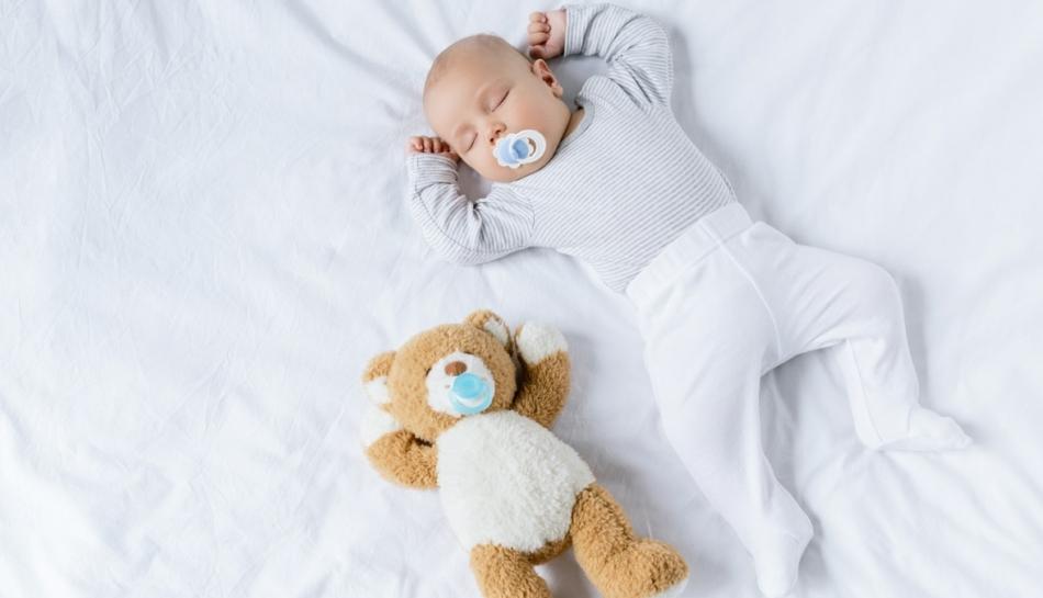Bambino dorme col suo gioco accanto