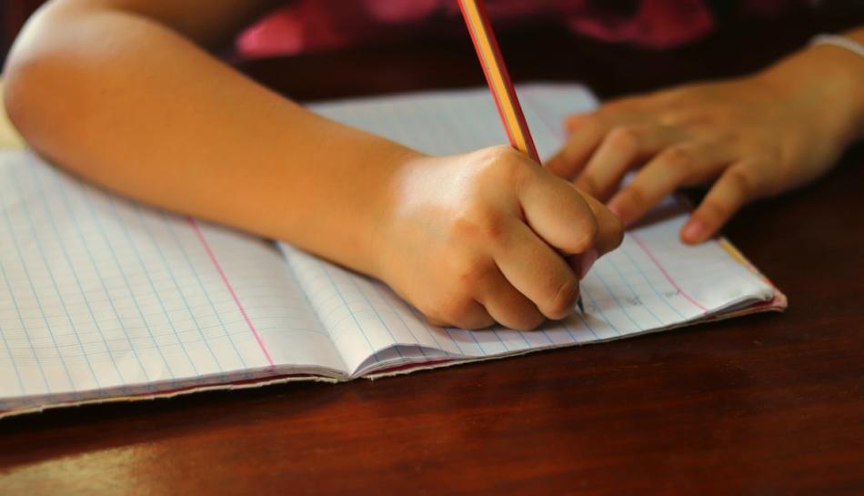 Bambino scrive durante un test per la disgrafia