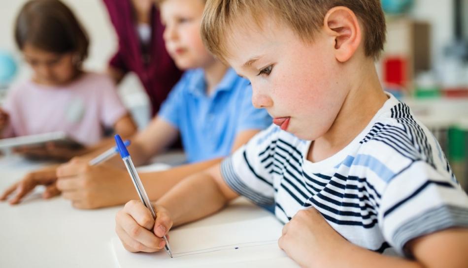 Bambino a scuola utilizza una penna