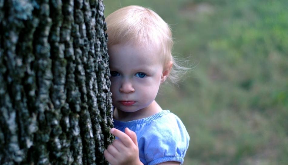 Bambina si nasconde dietro un albero