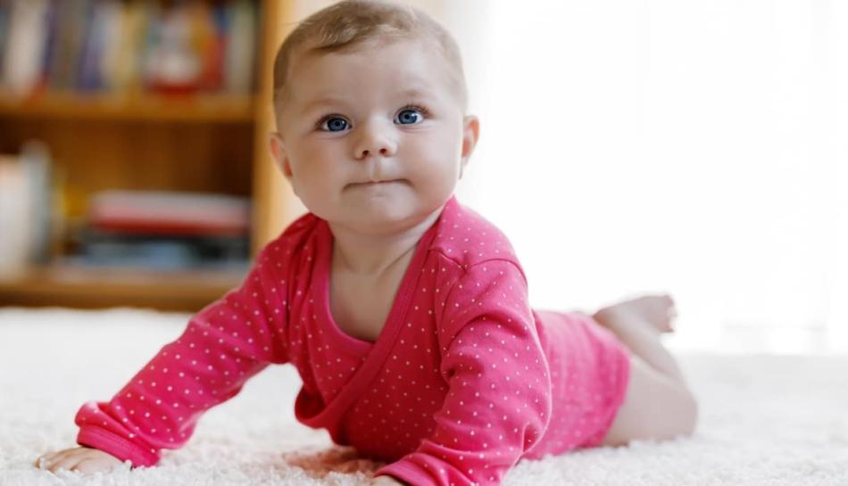 Bambina di 4 mesi cerca di gattonare
