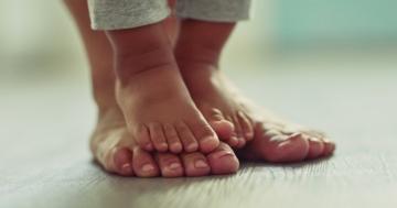 Piedi del bambino su quelli del genitore