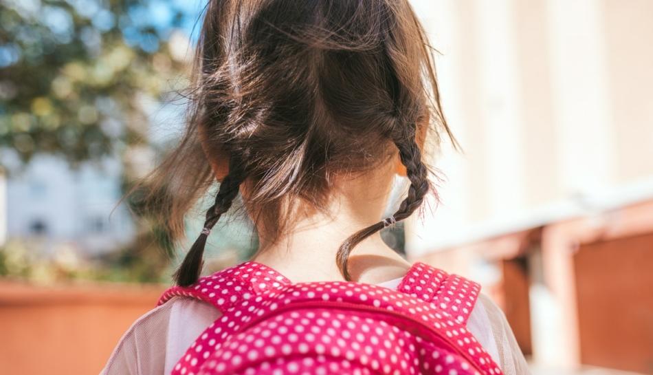 primo piano di bambina di spalle con zainetto
