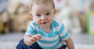 Bambino di 7 mesi seduto a terra
