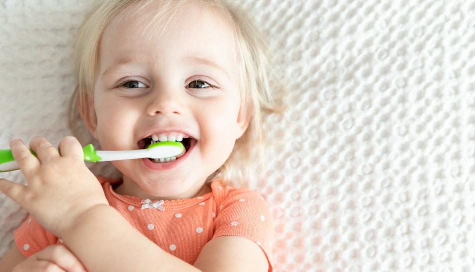 primo piano di bambina sdraiata con in mano uno spazzolino