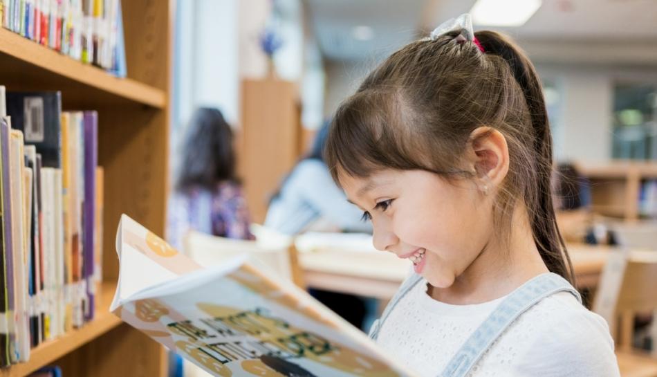 Bambina che legge un libro illustrato in biblioteca