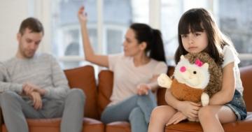 Bambina triste mentre sullo sfondo i suoi genitori litigano