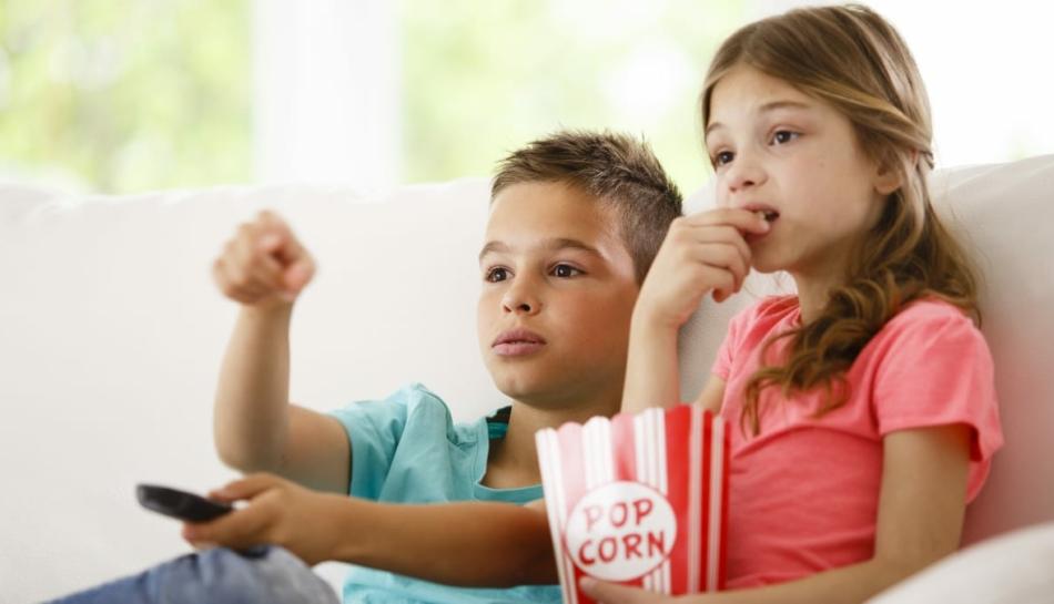 Bambini che guardano la televisione e la pubblicità sul divano
