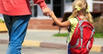 Papà e figlia di spalle davanti alla scuola per cominciare l'ambientamento