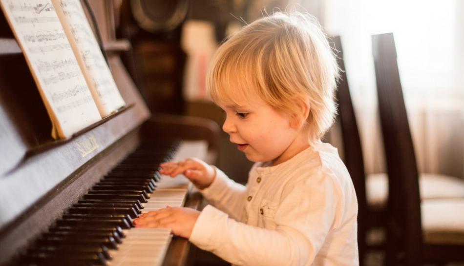 Bimbo suona il pianoforte durante la prima infanzia