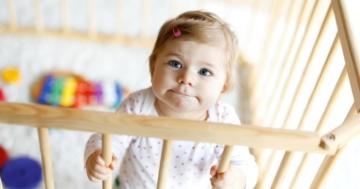 Bambina che sta in piedi dentro un box per giocare
