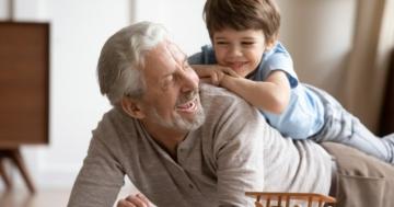 Nonno che gioca con un nipotino sulla schiena