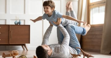 Bambino che viene sollevato in aria dal papà, entrambi per terra