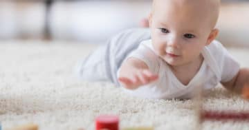 Bambino cerca di raggiungere un oggetto a terra