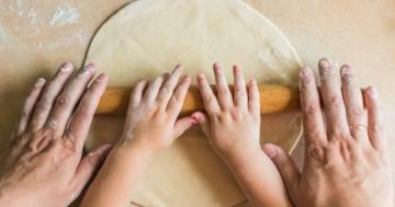 Bambino impasta in cucina con le mani assieme al genitore