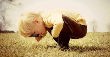 Bambino curioso usa la lente d'ingrandimento
