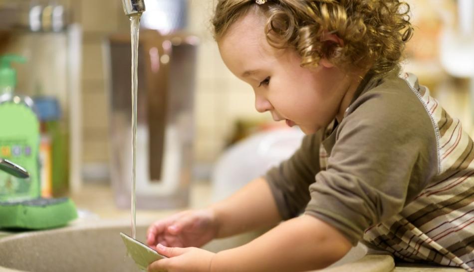 Bambina lava i piatti in autonomia