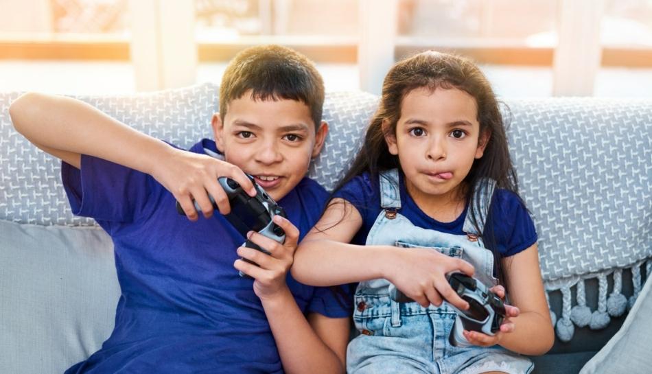 Due bambini sul divano che giocano ai videogiochi