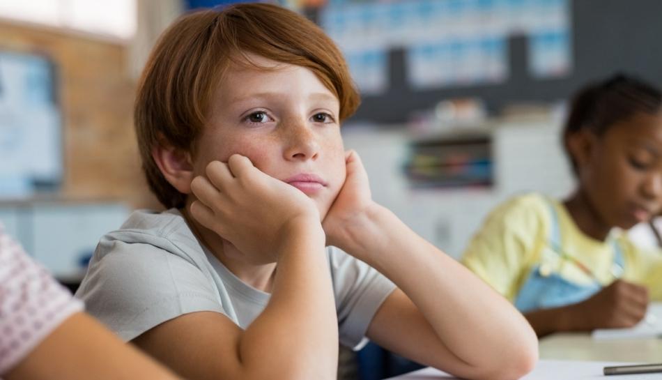 Bambino di carattere remissivo seduto al banco di scuola