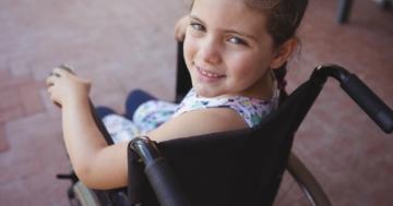 Primo piano di bambina con disabilità su sedia a rotelle