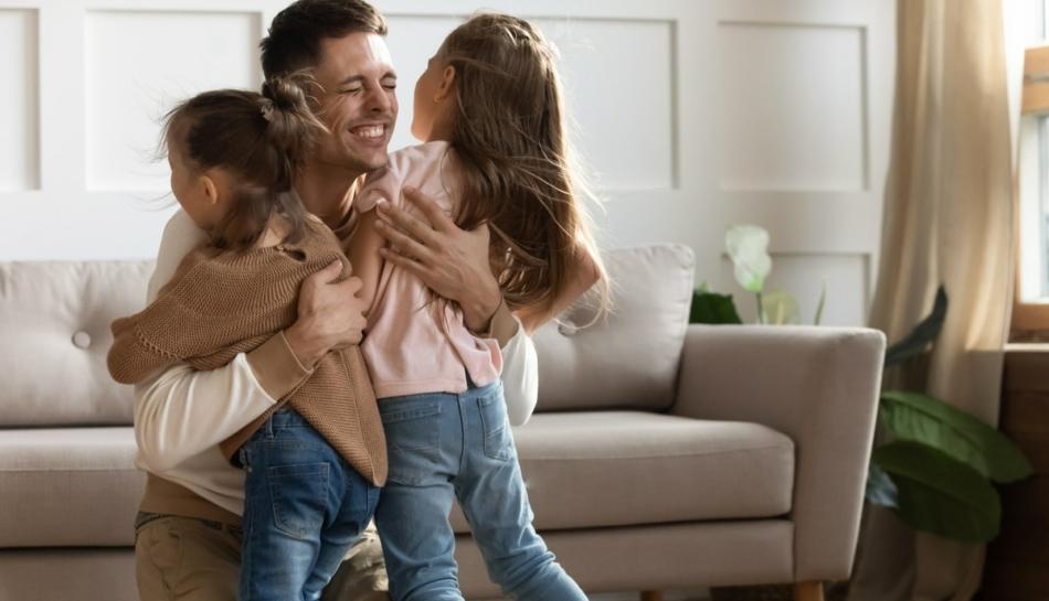 Papà che abbraccia felice le figlie